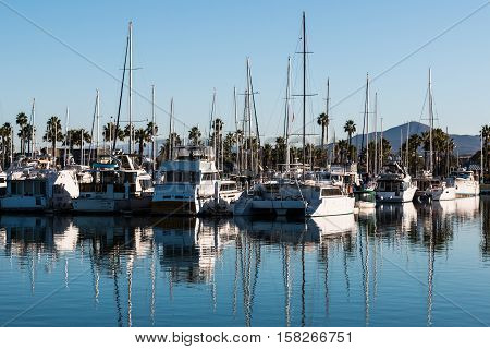 Boats moored in bay at the Chula Vista Bayfront park with mountain peak in the background.