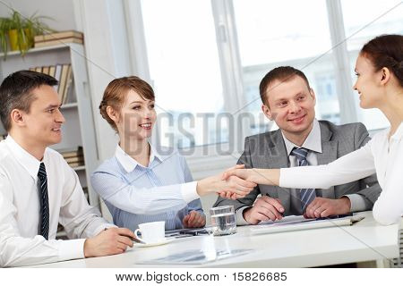 Image of business partners making an agreement with two men near by