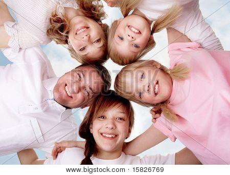 A young friendly family making circle while looking at camera