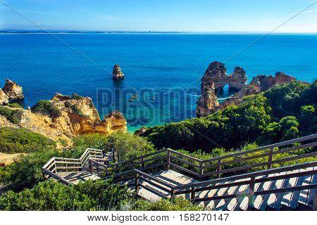 Wooden footbridge walkway to beautiful hidden beach Praia do Camilo in Lagos Algarve region Portugal