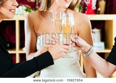 Vestidos de novia en la tienda de ropa para la boda; ella es elegir un vestido y es tintineo gafas con