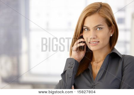 Businesswoman using cellphone, looking at camera, smiling.?