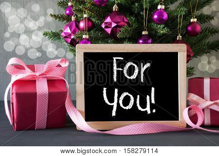 Christmas Tree With Rose Quartz Balls And Bokeh Effect. Gifts Or Presents In The Front Of Cement Background. Chalkboard With English Text For You