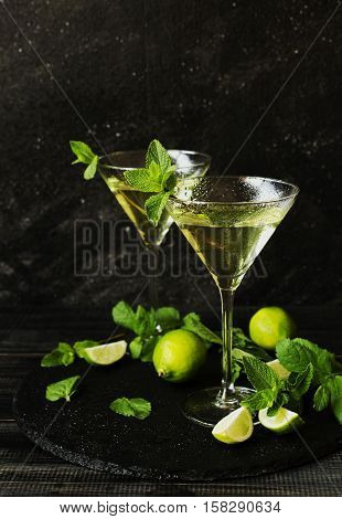 Martini or mint liqueur with lime on a black background in a martini glass with smoke, selective focus