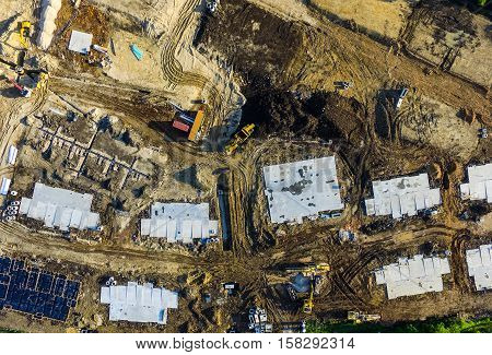 Looking straight down above construction with foundation squares and pipelines and construction vehicles Austin Texas USA aerial view