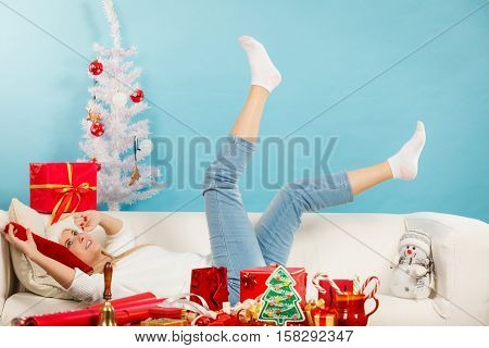 Seasonal concept. Happy blonde woman wearing santa hat lying on sofa with presents christmas tree in background indoor shot.
