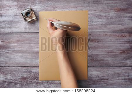 Female hand with feather writing on sheet of paper