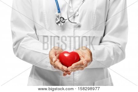 Young female cardiologist holding plastic heart on white background