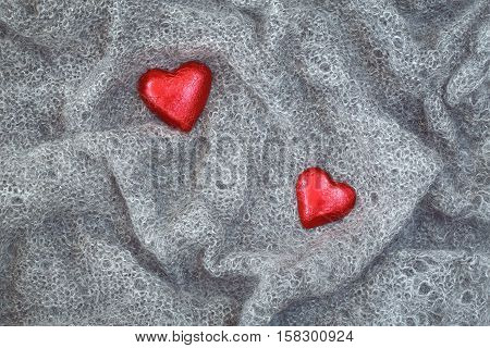 Closeup macro texture of grey knitted wool fabric material shawl scarf with red candy hearts on top clothing background with wrinkles and folds Valentine holiday card love concept