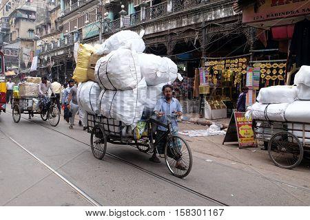 KOLKATA, INDIA - FEBRUARY 11: Worker pulling bale on tricycle rickshaw along a busy street in Kolkata, India on February 11, 2016.