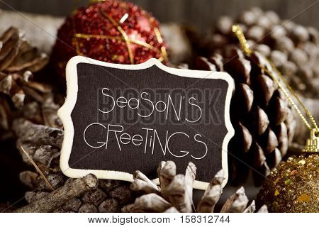 the text seasons greetings written in a black signboard and some pine cones and christmas balls
