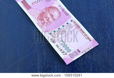 Indian currency two thousand rupees, with focus on the number 2000, on a wooden background.