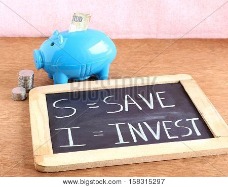 Save and invest concept, highlighted through text wrote on a chalkboard.
