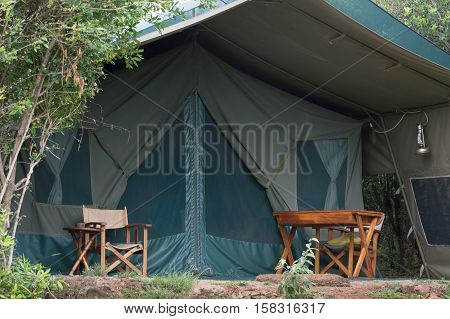 The outside of a canvas safari tent with chairs and desk in sub-Saharan Africa