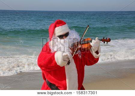 Santa Claus plays his Violin on the beach. Santa plays music. Santa Claus in music concert on the beach. Santa Claus vacation. Santa plays the violin. Violin. violin music.