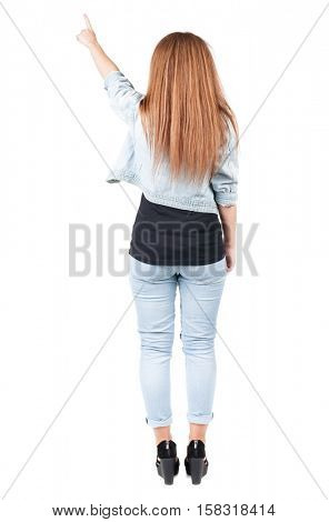 Back view of  pointing woman. beautiful redhead girl in jeans. Rear view people collection.  backside view of person.  Isolated over white background.