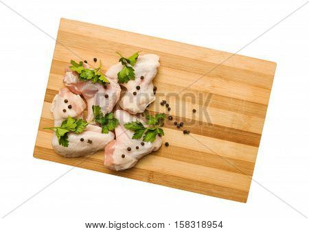Raw chicken wings with spices on a cutting board with clipping path. Top view.