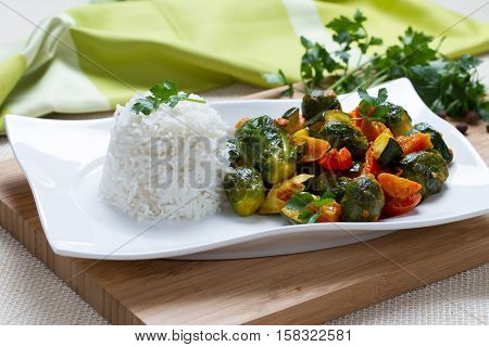 Rice and vegetables on white plate with with herbs and pepper on wooden bord, horizontal view