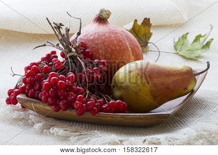 Autumn gifts. Still life with pumpkin, viburnum and pear on wooden plate