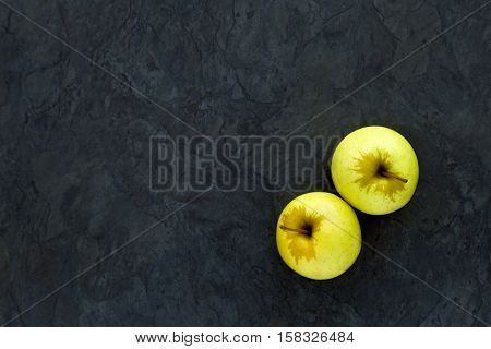 Two delicious ripe apples on a grey slate background with lots of copy space
