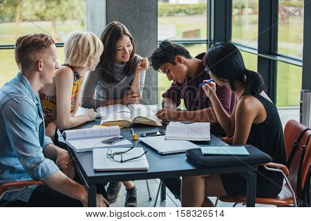 Multiracial Students Studying Together In A Library