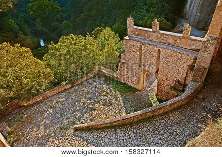 Sorano, Grosseto, Tuscany, Italy: view of the path and the old staircase that leads from the forest to the ancient village with the medieval city gate Porta dei Merli