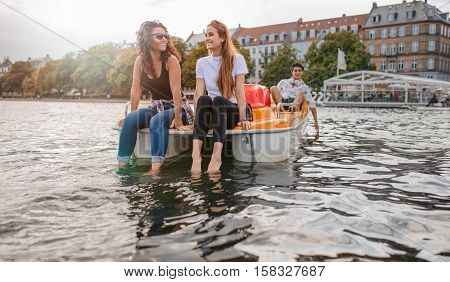 Outdoors shot of young female friends sitting in front pedal boat and putting their feet in water with man in background. Teenage friends enjoying boating in the lake.