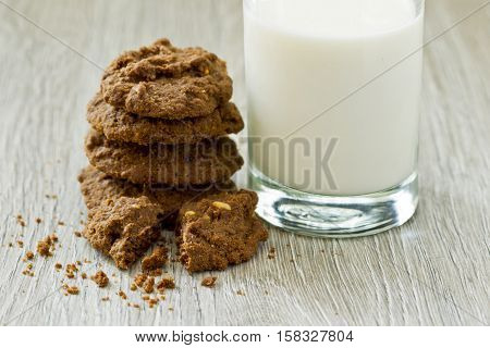 Stack of freshly baked American nut cookies and a glass of milk