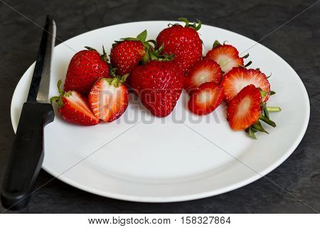 Sliced strawberries arranged on a white plate with a sharp knife to the side