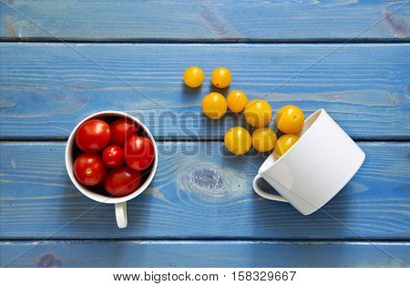 two white cups pouring red and yellow tomatoes onto a blue wooden textured background