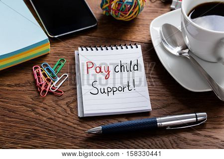 High Angle View Of Pay Child Support Concept Written On Notepad At Wooden Desk