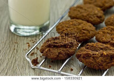 Freshly baked cookies on a cooling rack and a glass of milk