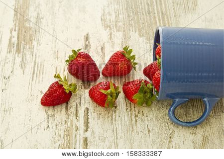 Blue mug pouring out red ripe strawberries onto a white wooden background