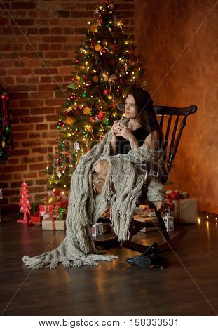 Young woman sits in a rocking-chair having wrapped up with a plaid near Christmas-tree. She holds a cup in hand. Room is specially decorated by Christmas. Woman has taken off footwear and has a rest.