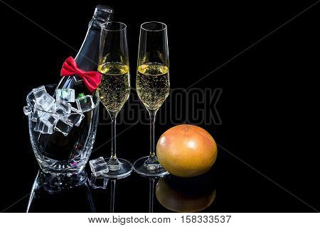 Bottle of champagne in an ice bucket and wineglasses with grapefruit