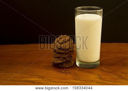 stacked chocolate American nut cookies next to a glass of milk