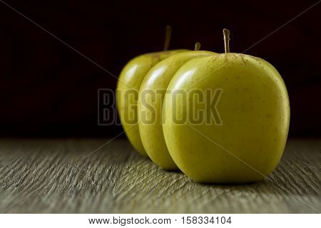 Sweet golden delicious apples in on a textured board in soft window light