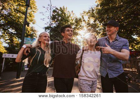 Four Friends Strolling In Amusement Park