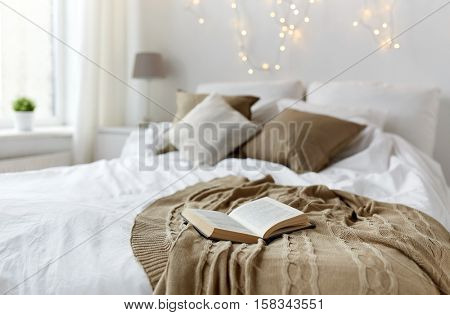 coziness, comfort, interior and holidays concept - cozy bedroom with bed and christmas garland lights at home