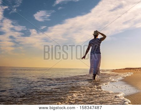 Young woman wearing hat and white skirt strolling along the beach towards the rising Sun