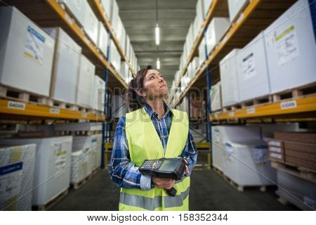 Puzzled woman in warehouse working with hand scanner and looking for one particular item. First in first out Last in last out team working together concept photo.