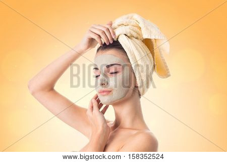 gorgeous Young girl takes care her skin with cleansing mask on face and towel on head isolated on white background. Health care concept. Body care concept. Young woman with healthy skin.