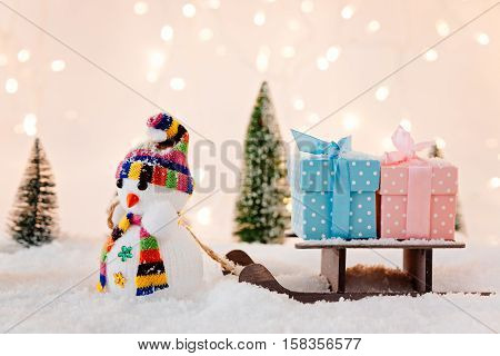 Toy Snowman Pulling Small Wooden Sleigh With A Christmas Gifts.