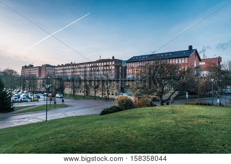 Chalmers university of technology, early in the morning about to wake up. Passing airplain leaving vapor trails in the sky.