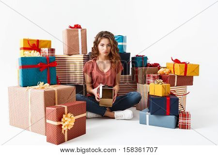 Young upset beautiful curly girl sitting on floor among gift boxes showing one she opened is empty Isolated Copy space