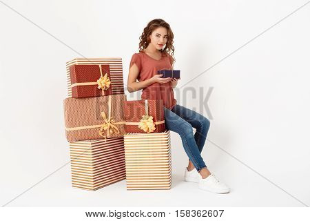 Young beautiful girl sitting on big gift box holding smaller one in hands Isolated Copy space