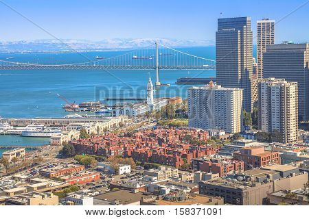 Aerial view close up of San Francisco skycraper, Embarcadero and Oakland Bridge from top of Coit Tower on Telegraph Hill on a sunny day. California, United States.