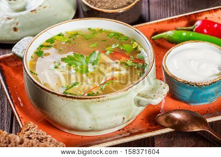Vegetable soup broth with noodles herbs parsley and vegetables in bowl with sour cream spice pepper dried thyme and bread on dark wooden background healthy food