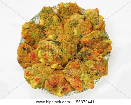 Healthy baked vegan vegetable pakoras on plate, top view.