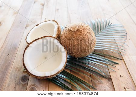 coconut and green leaf on wooden background